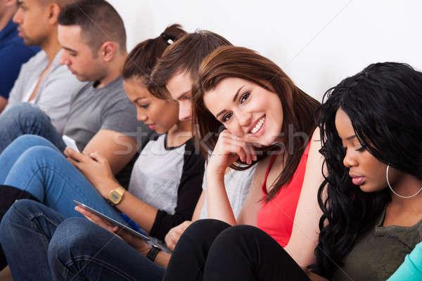 Gyönyörű főiskolai hallgató ül osztálytársak portré fal Stock fotó © AndreyPopov