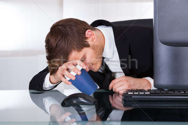 Tired Businessman Holding Coffee Cup At Desk Stock photo © AndreyPopov