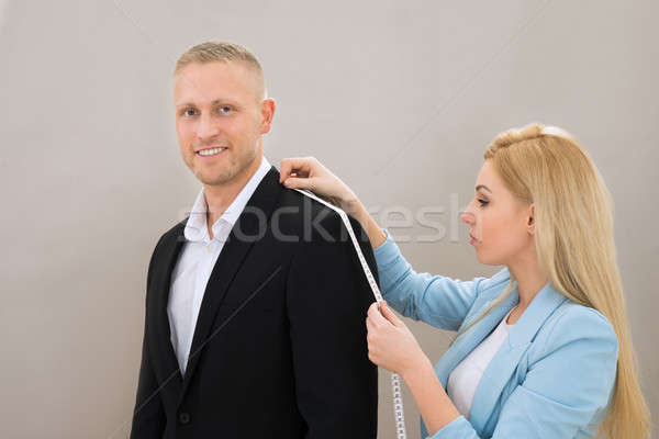Stock photo: Female Tailor Taking Measurement Of Suit