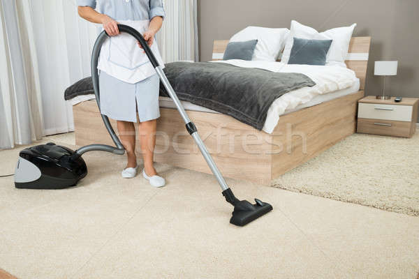 Vrouwelijke huishoudster schoonmaken stofzuiger hotelkamer vrouw Stockfoto © AndreyPopov