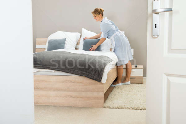 Young Maid Arranging Pillow On Bed Stock photo © AndreyPopov