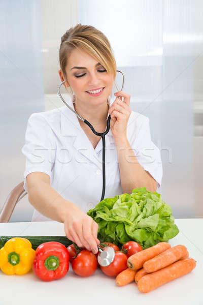 Female Dietician Examining Vegetables Stock photo © AndreyPopov