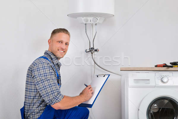 Stock photo: Plumber Writing Meter Reading On Clipboard