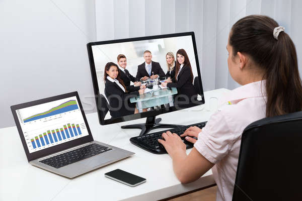 Stock photo: Businesswoman Videoconferencing On Computers