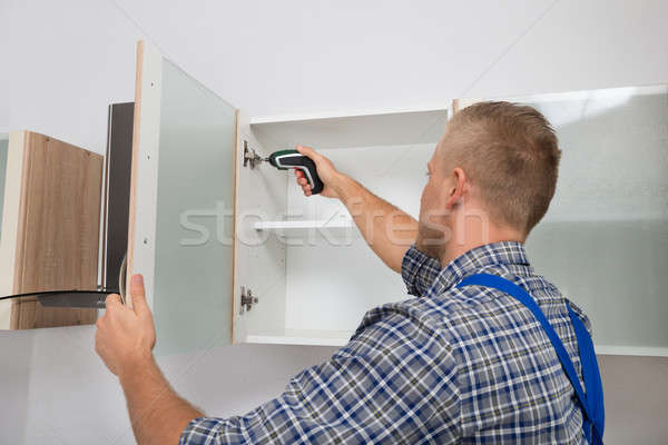 Carpenter Drilling In Cabinet Stock photo © AndreyPopov