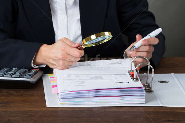 Accountant Scrutinizing Bills With Magnifying Glass Stock photo © AndreyPopov