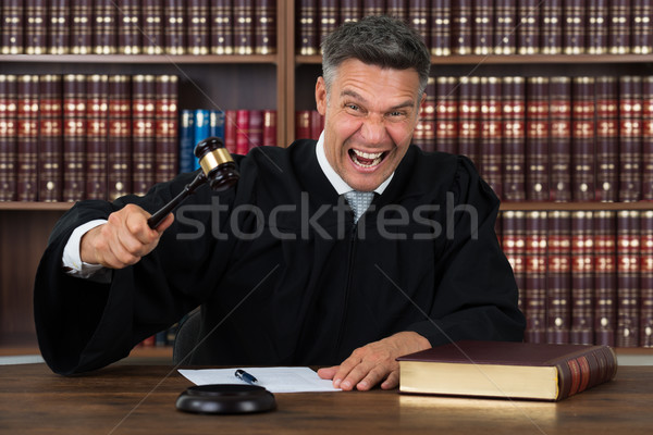Angry Judge Striking His Gavel At Table Stock photo © AndreyPopov