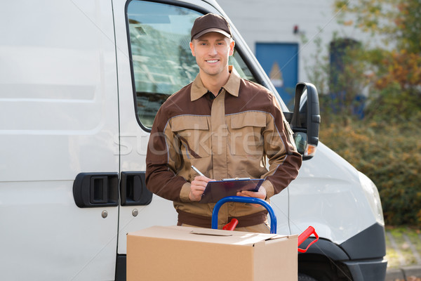Delivery Man With Parcels And Clipboard Against Truck Stock photo © AndreyPopov