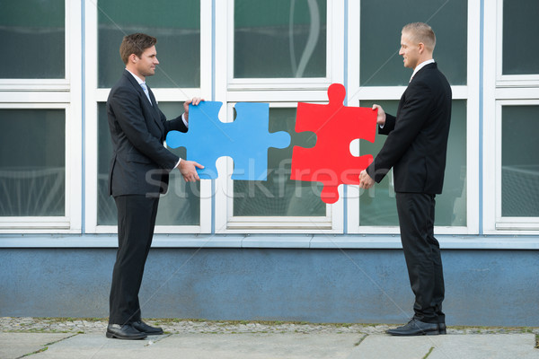 Businessmen Joining Jigsaw Pieces Outside Office Stock photo © AndreyPopov