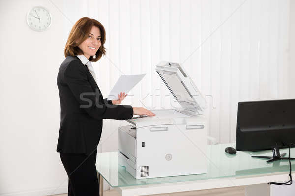 Businesswoman Copying Paper On Photocopy Machine Stock photo © AndreyPopov