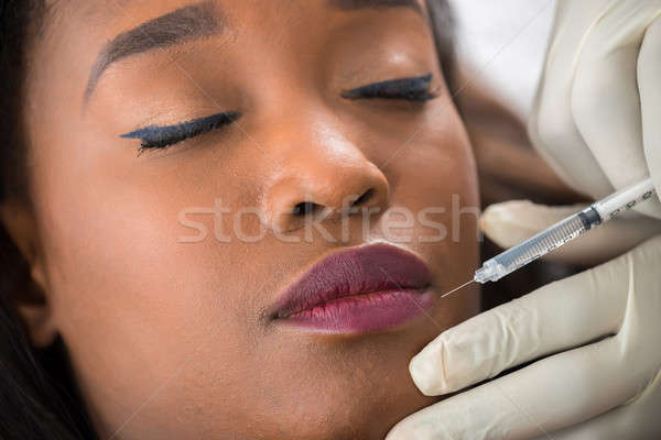 Person Hand Injecting Syringe On Young Woman Face Stock photo © AndreyPopov