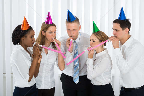 Businesspeople Blowing Party Blower In Office Stock photo © AndreyPopov