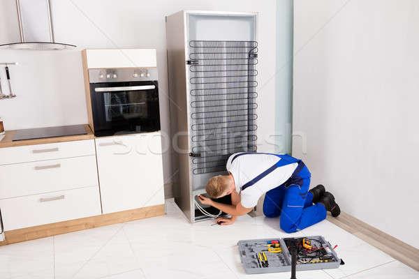 Férfi technikus hűtőszekrény fiatal csavarhúzó otthon Stock fotó © AndreyPopov