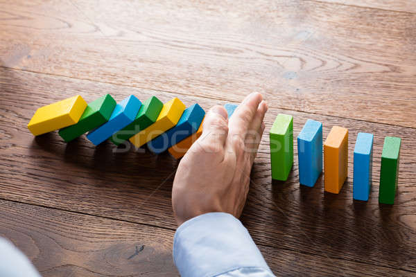 Person Hand Stopping Dominoes Stock photo © AndreyPopov