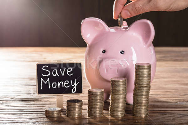 Person Inserting Coin In Piggybank Showing Save Money Concept Stock photo © AndreyPopov