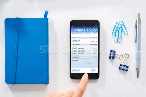 Woman Doing Online Banking On Mobile Phone Stock photo © AndreyPopov