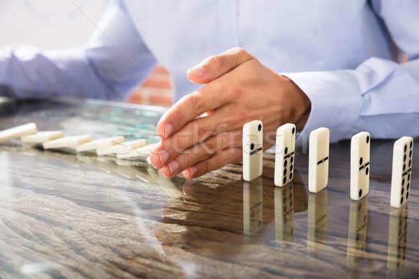 Businessman Stop Dominoes On Desk Stock photo © AndreyPopov