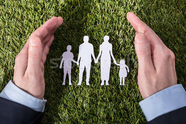 Person Protecting Family Paper Cut Out On Grass Stock photo © AndreyPopov