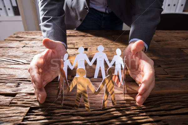 Businessperson Protecting Paper Cut Out Figures Stock photo © AndreyPopov