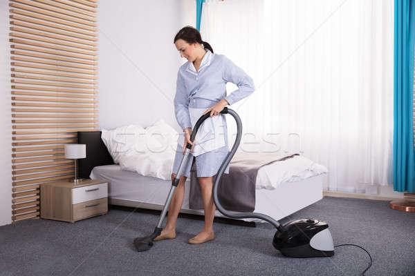 Governanta limpeza tapete aspirador de pó feliz jovem Foto stock © AndreyPopov