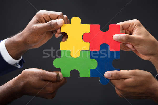 Hands Combining White Puzzle Pieces Stock photo © AndreyPopov