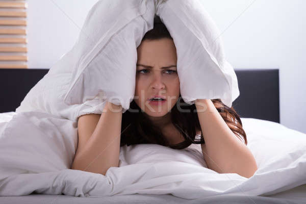 Stock photo: Woman On Bed Covering Her Ear With Bedsheet