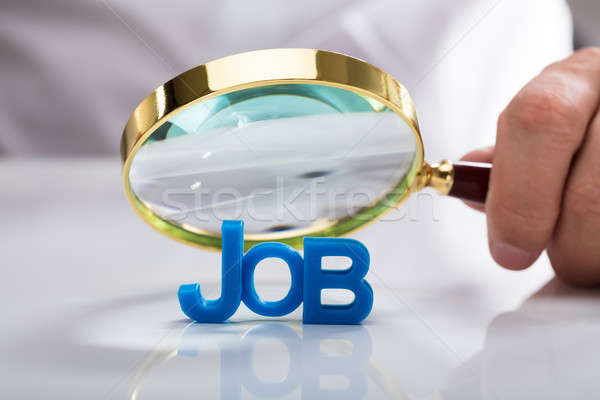 Businessman holding magnifying glass over job word Stock photo © AndreyPopov
