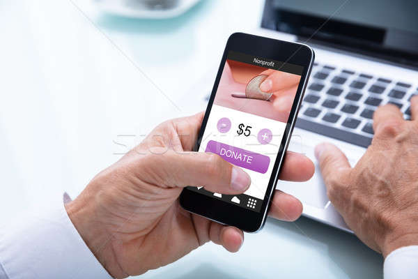 Businessman Donating Money Online On Mobile Phone Stock photo © AndreyPopov