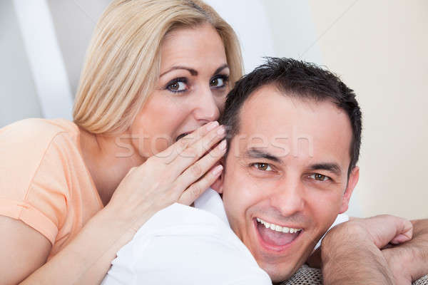 Mid-adult man and woman sharing a secret Stock photo © AndreyPopov