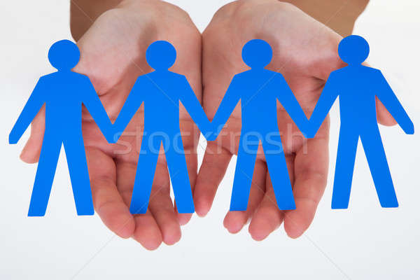 Stock photo: Male Hand Holding Human Figure Cutout