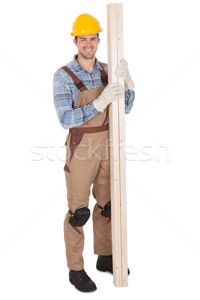 Worker wearing hard hat and holding timber Stock photo © AndreyPopov