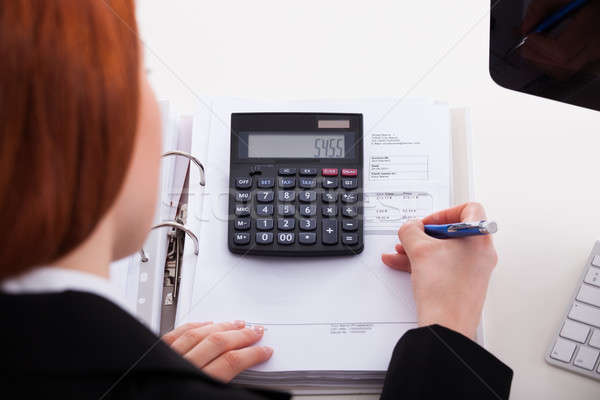 Businesswoman Using Calculator At Office Desk Stock photo © AndreyPopov