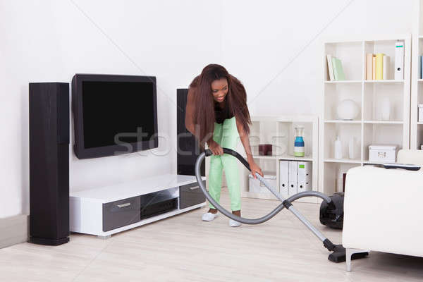 Kadın temizlik ev elektrikli süpürge tam uzunlukta genç kadın Stok fotoğraf © AndreyPopov