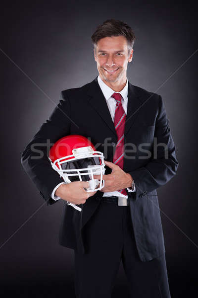 Businessman Holding Rugby Helmet Stock photo © AndreyPopov