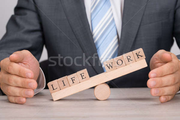 Businessman Covering Imbalance Between Life And Work On Seesaw Stock photo © AndreyPopov