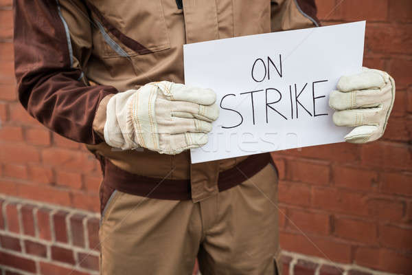 Worker Holding Placard With The Text On Strike Stock photo © AndreyPopov