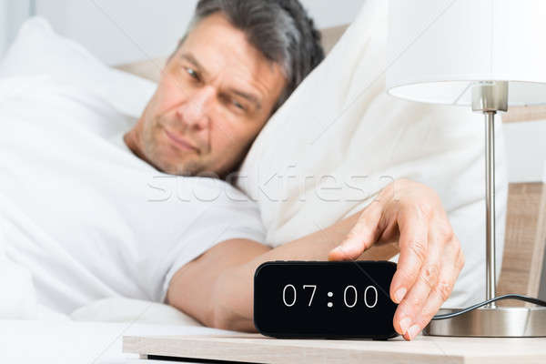 Mature Man Turning Off Clock Stock photo © AndreyPopov