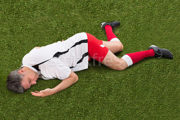 Soccer Player Lying On Grass Stock photo © AndreyPopov