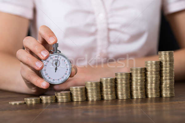 Businessperson With Stopwatch And Stack Of Coins Stock photo © AndreyPopov
