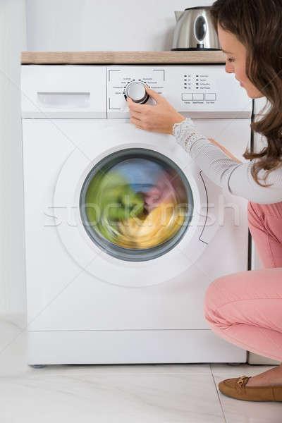 Stock photo: Woman Pressing Button Of Washing Machine
