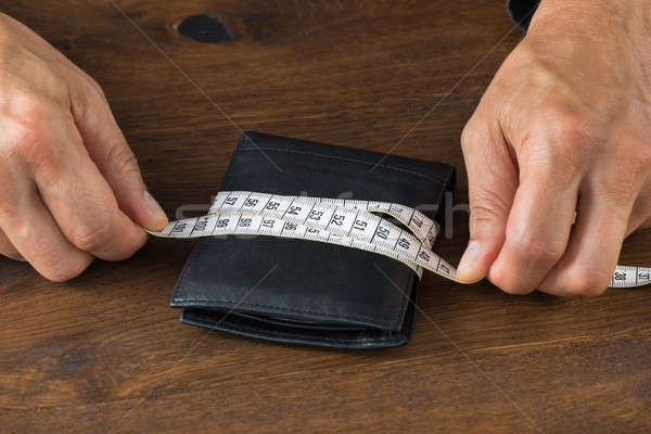 Businessman Wrapping Wallet With Tape Measure Stock photo © AndreyPopov