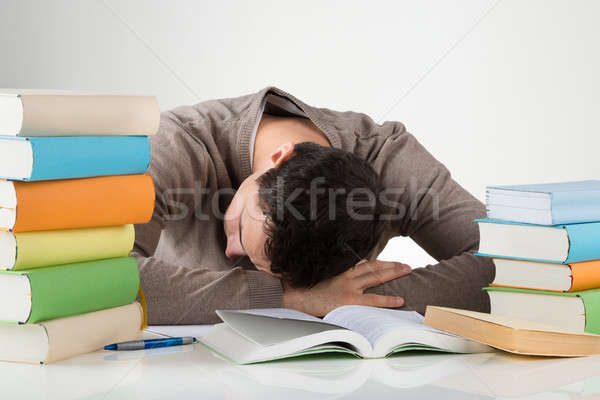 Tired Student Leaning On Desk While Studying Stock photo © AndreyPopov