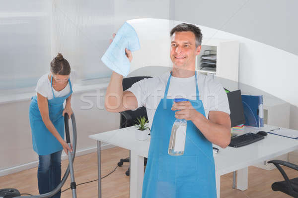 Male Worker Cleaning Glass While Female Worker Vacuuming Stock photo © AndreyPopov