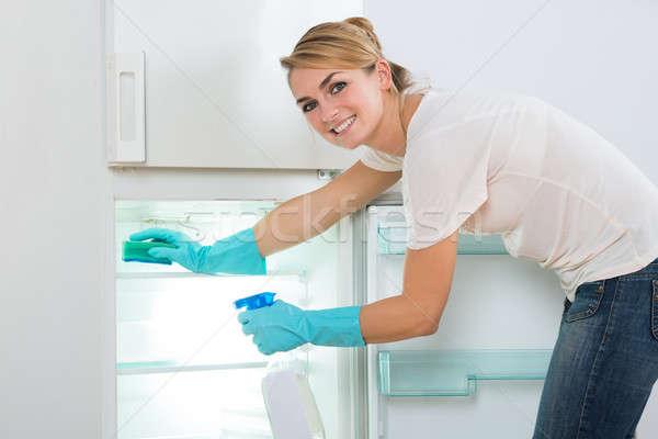 Stockfoto: Glimlachende · vrouw · schoonmaken · koelkast · spons · spray · portret