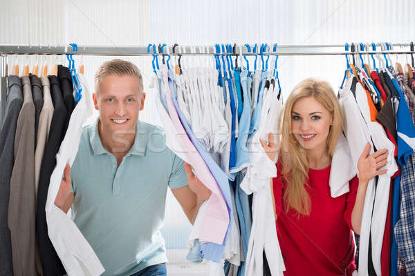 Couple Peeking Through Shirts Hanging From Rack Stock photo © AndreyPopov