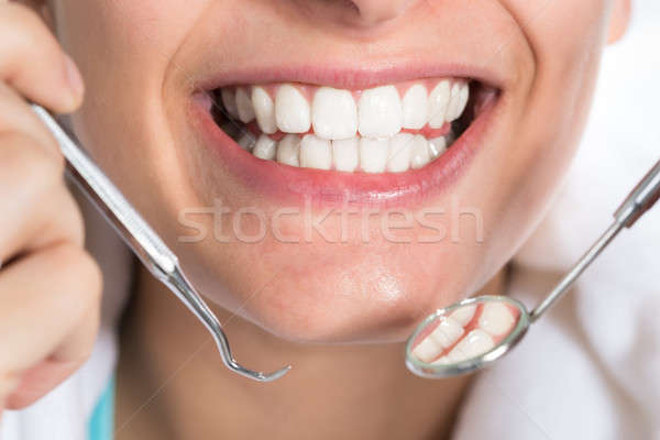 Woman Holding Dental Tools While Showing Healthy White Teeth Stock photo © AndreyPopov