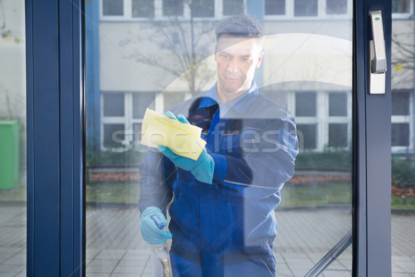 Happy Mature Male Worker Cleaning Glass With Rag Stock photo © AndreyPopov