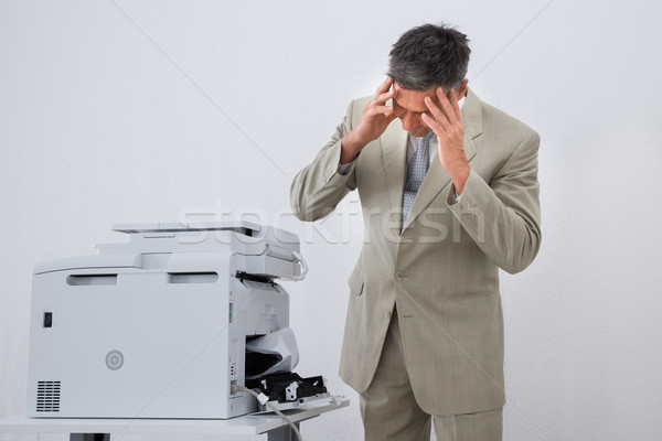 Businessman Looking At Paper Stuck In Printer Stock photo © AndreyPopov