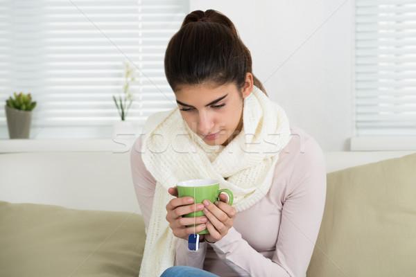 Sad Woman Holding Tee Mug On Sofa At Home Stock photo © AndreyPopov