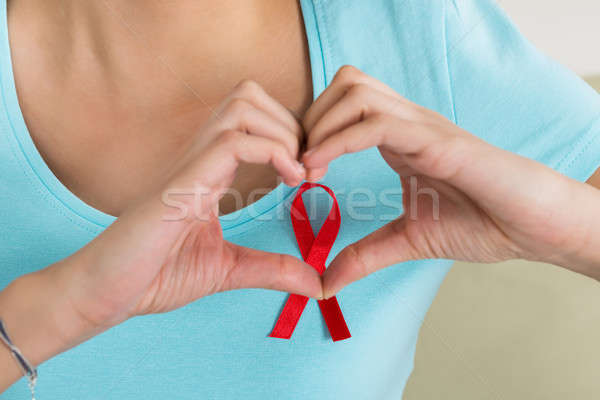 Woman Making Heart Shape In Front Of Aids Awareness Ribbon Stock photo © AndreyPopov